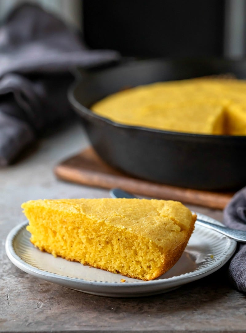 Slice of cornbread on a white plate next to a cast iron skillet