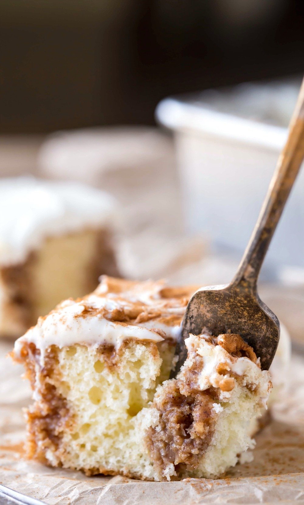 Piece of Cinnamon Roll Poke Cake with a fork in it