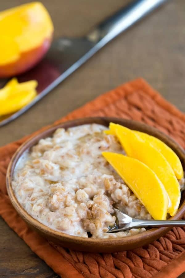 A bowl of Coconut Mango Breakfast Farro with a spoon in it.