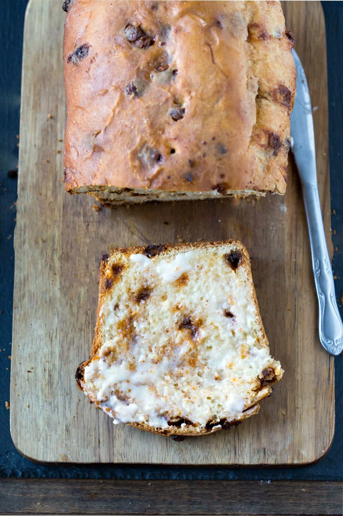 Slice of cinnamon chip bread on a wooden cutting board