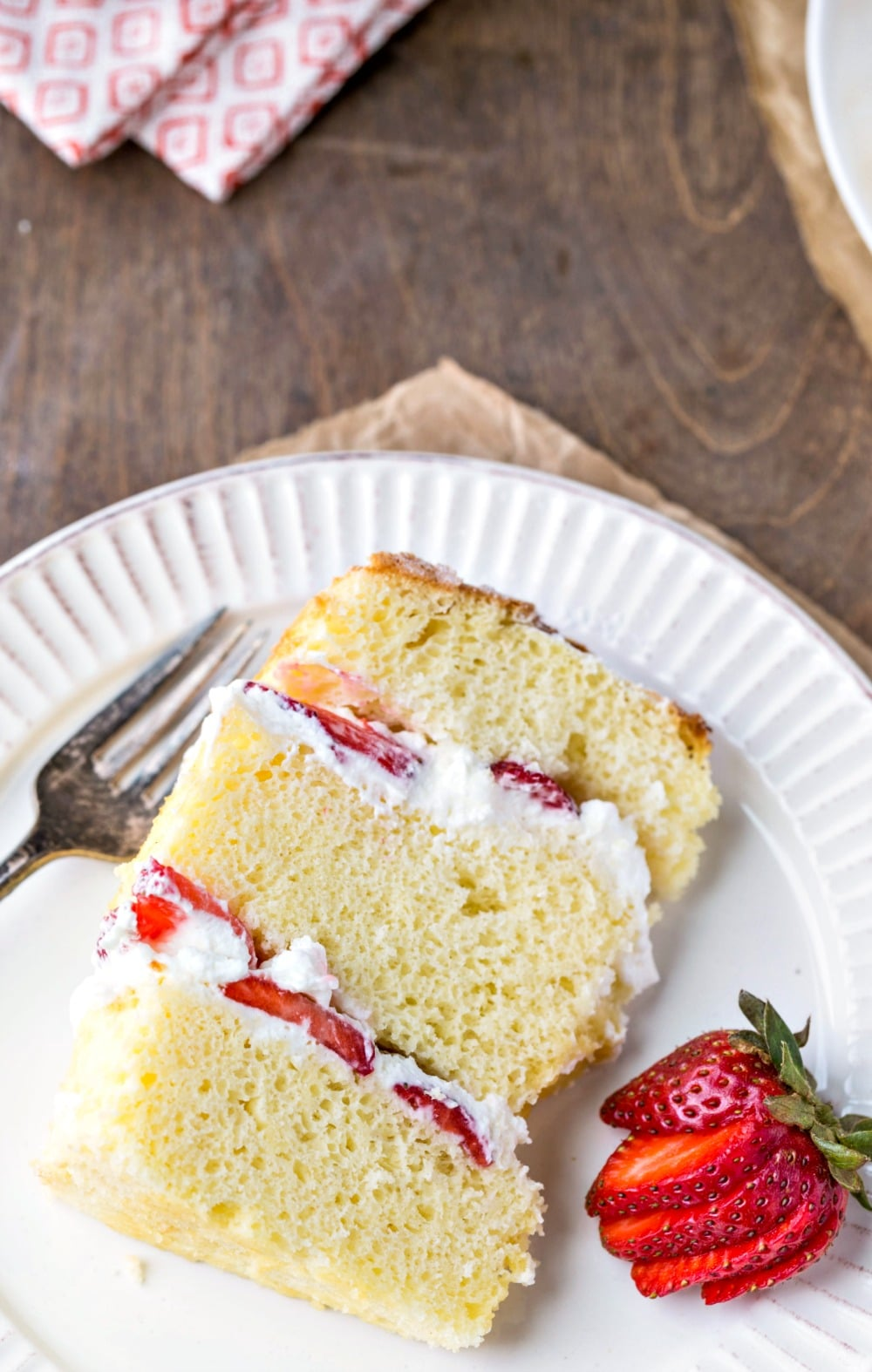 Slice of strawberry shortcake cake on a white plate next to a cut strawberry