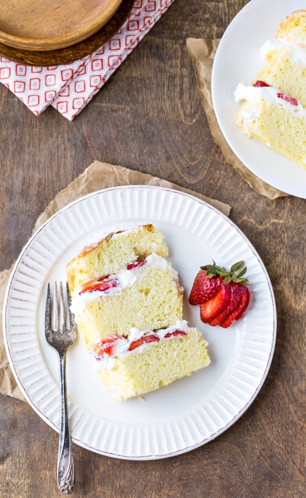 Slice of strawberry shortcake cake on a white plate next to a fork and a strawberry