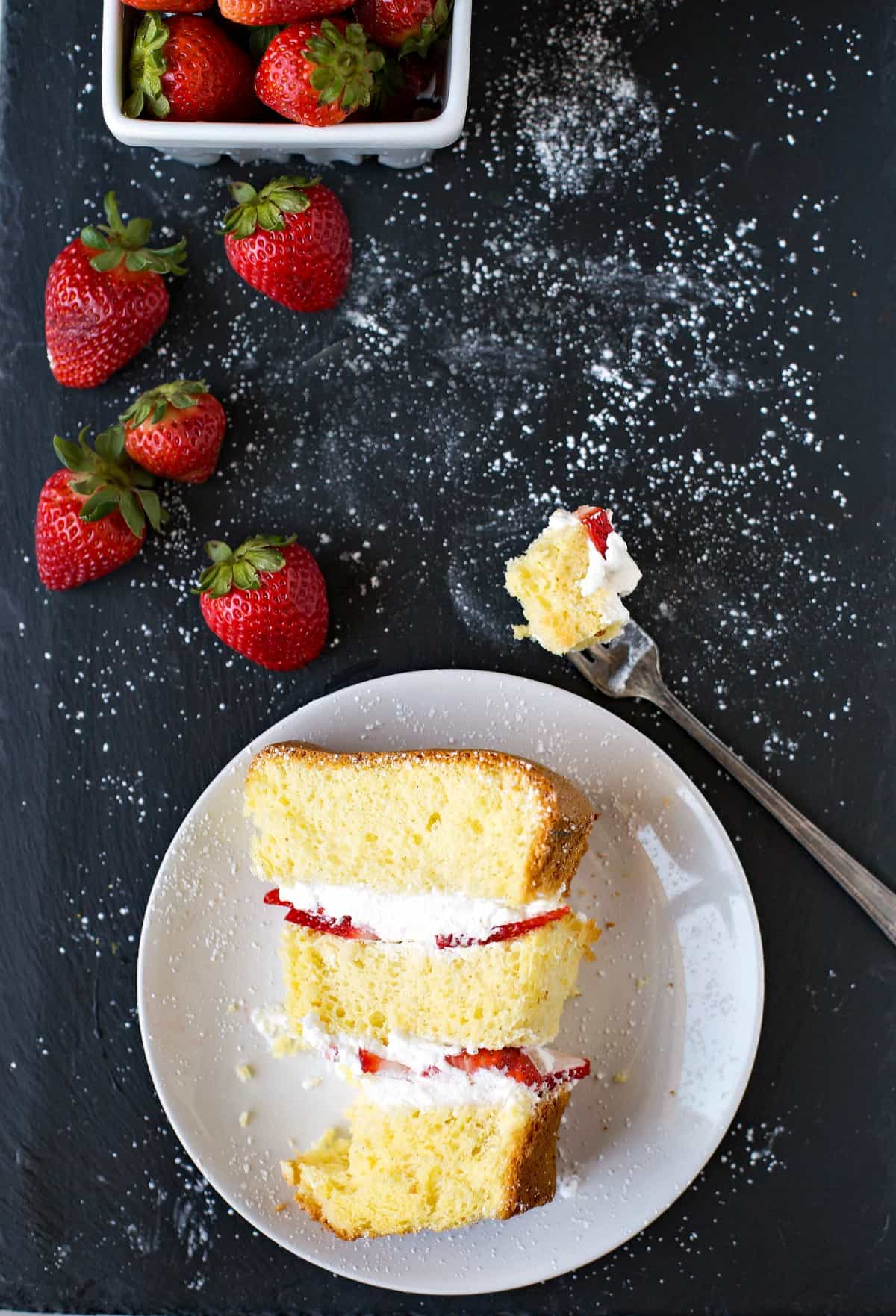 Strawberry Shortcake Cake slice on a plate next to strawberries