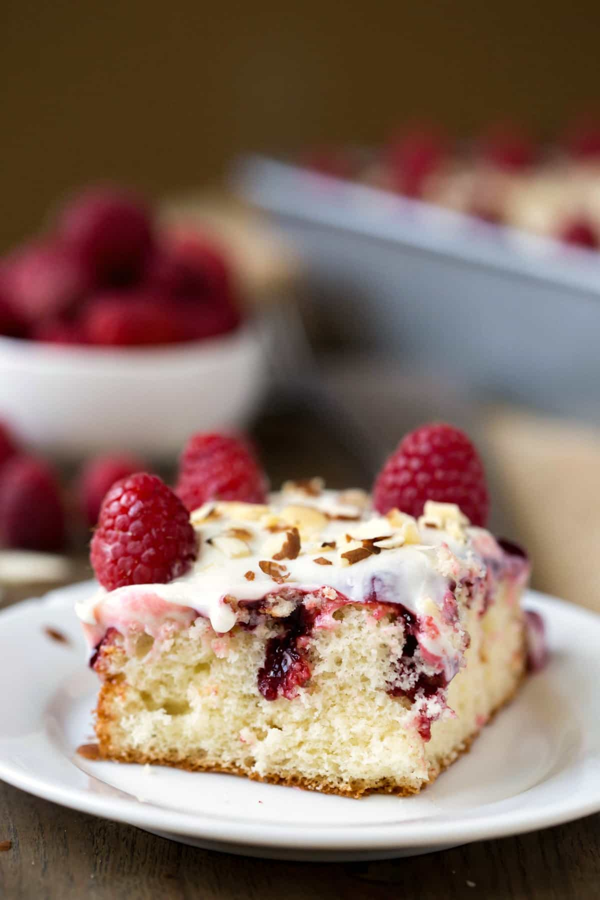 Slice of White Raspberry Poke Cake on a white plate next to a bowl of raspberries