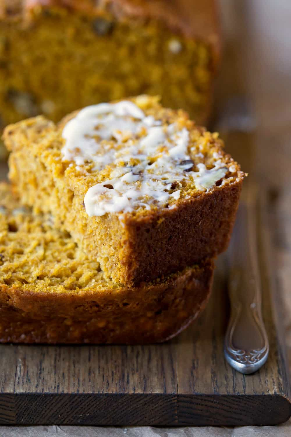 Cut slice of Buttermilk Pumpkin Spice Bread with butter on top