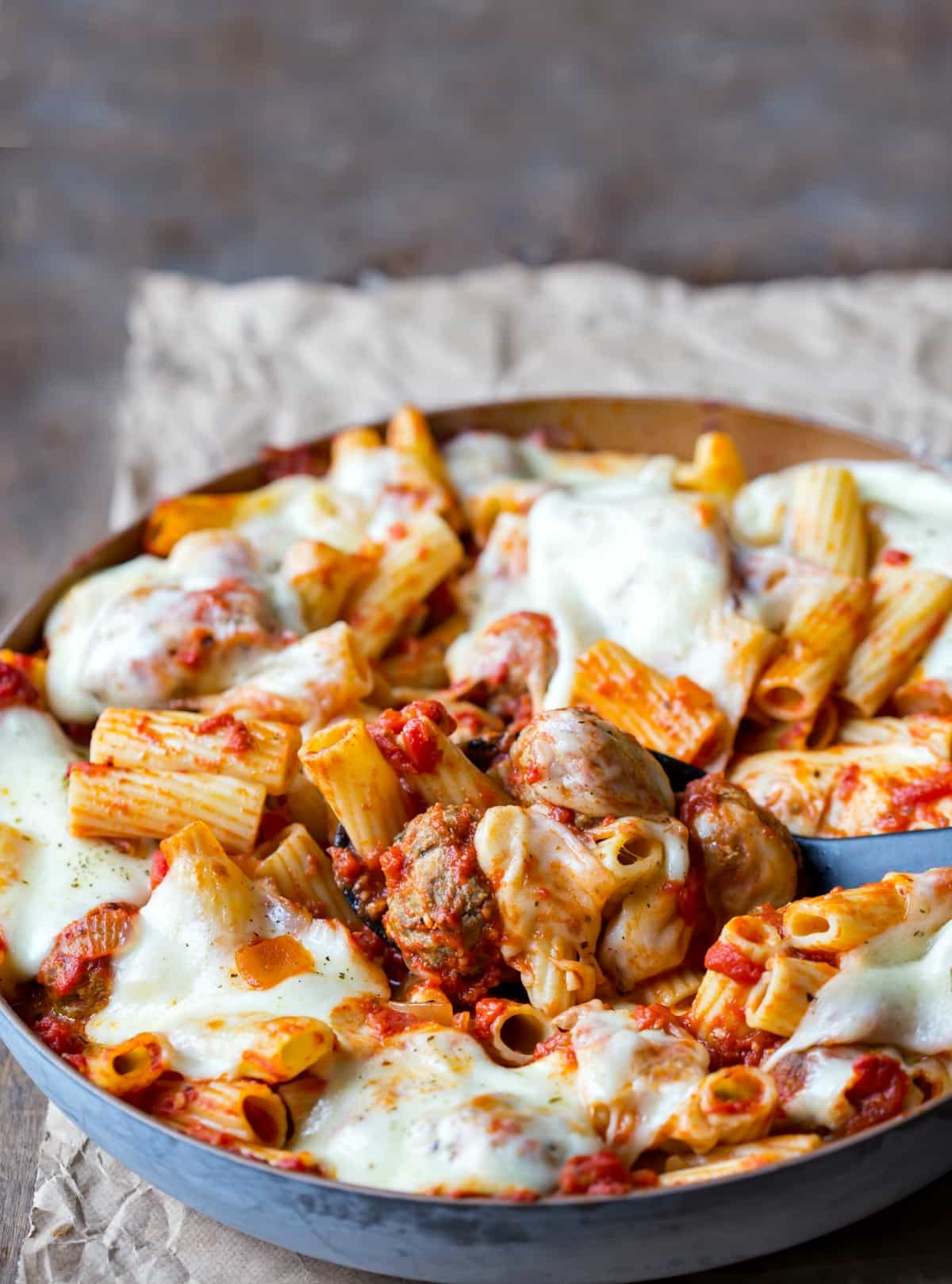 Skillet of meatball pasta on a piece of brown parchment paper