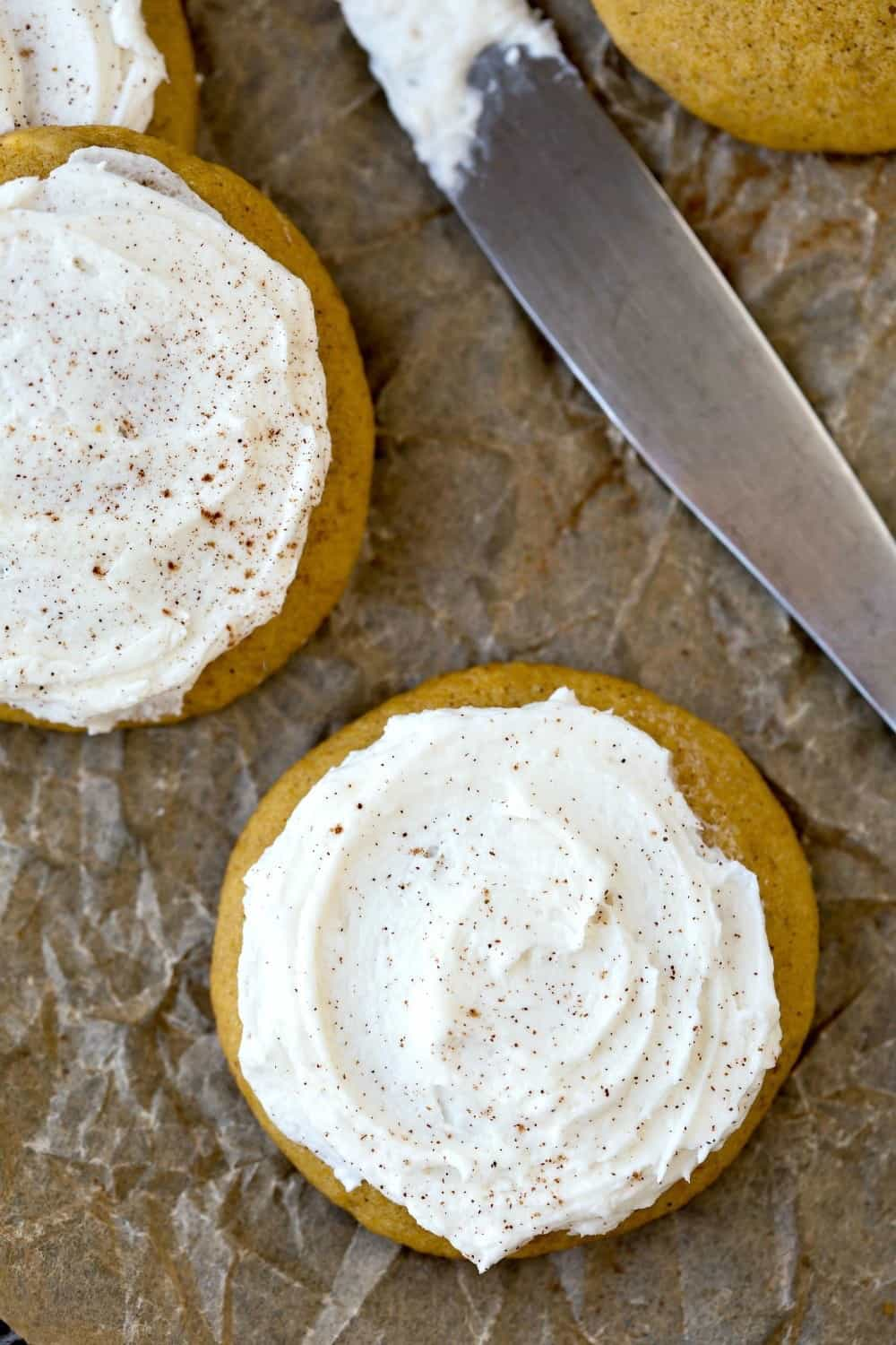 Melt-In-Your-Mouth Frosted Pumpkin Cookies next to a silver knife