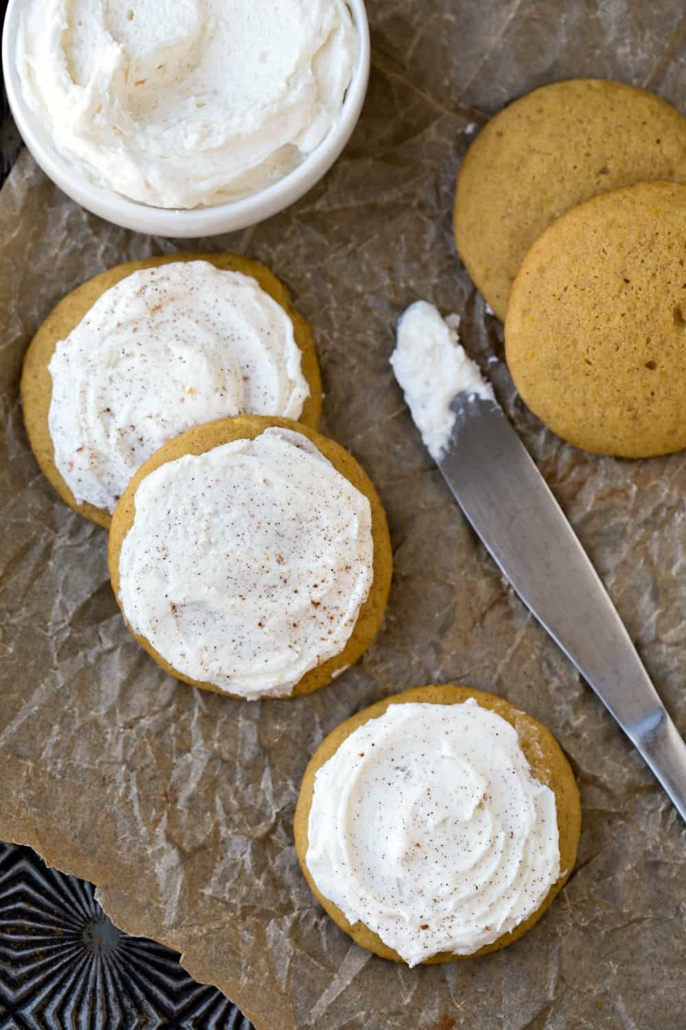 Melt-In-Your-Mouth Frosted Pumpkin Cookies on a piece of brown parchment paper