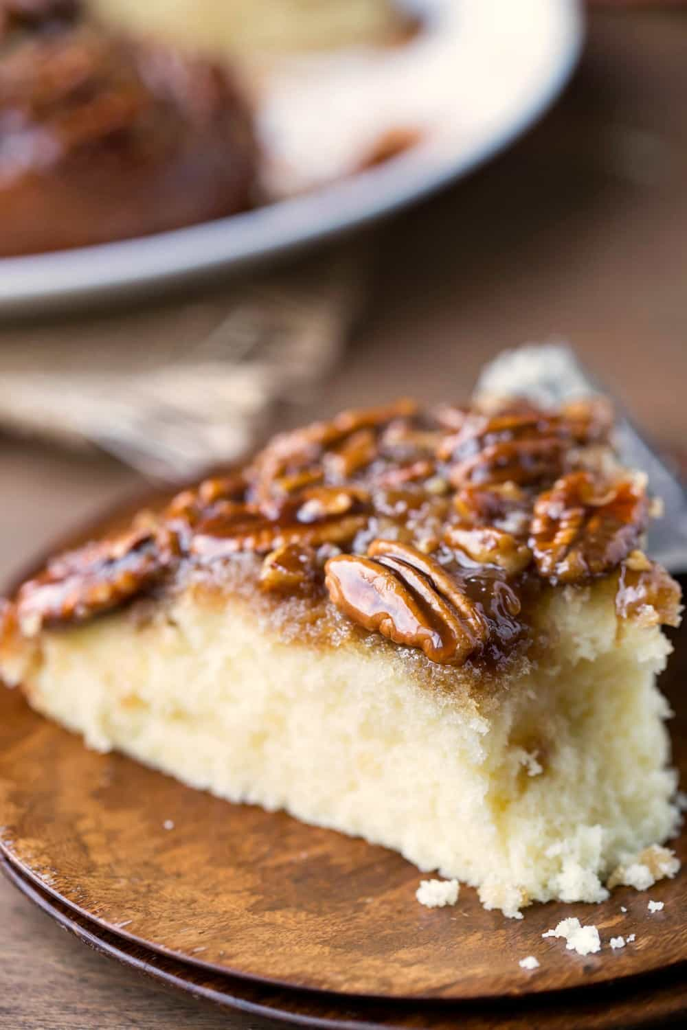 Slice of Pecan Pie Upside-Down Cake on a wooden plate with a bite missing