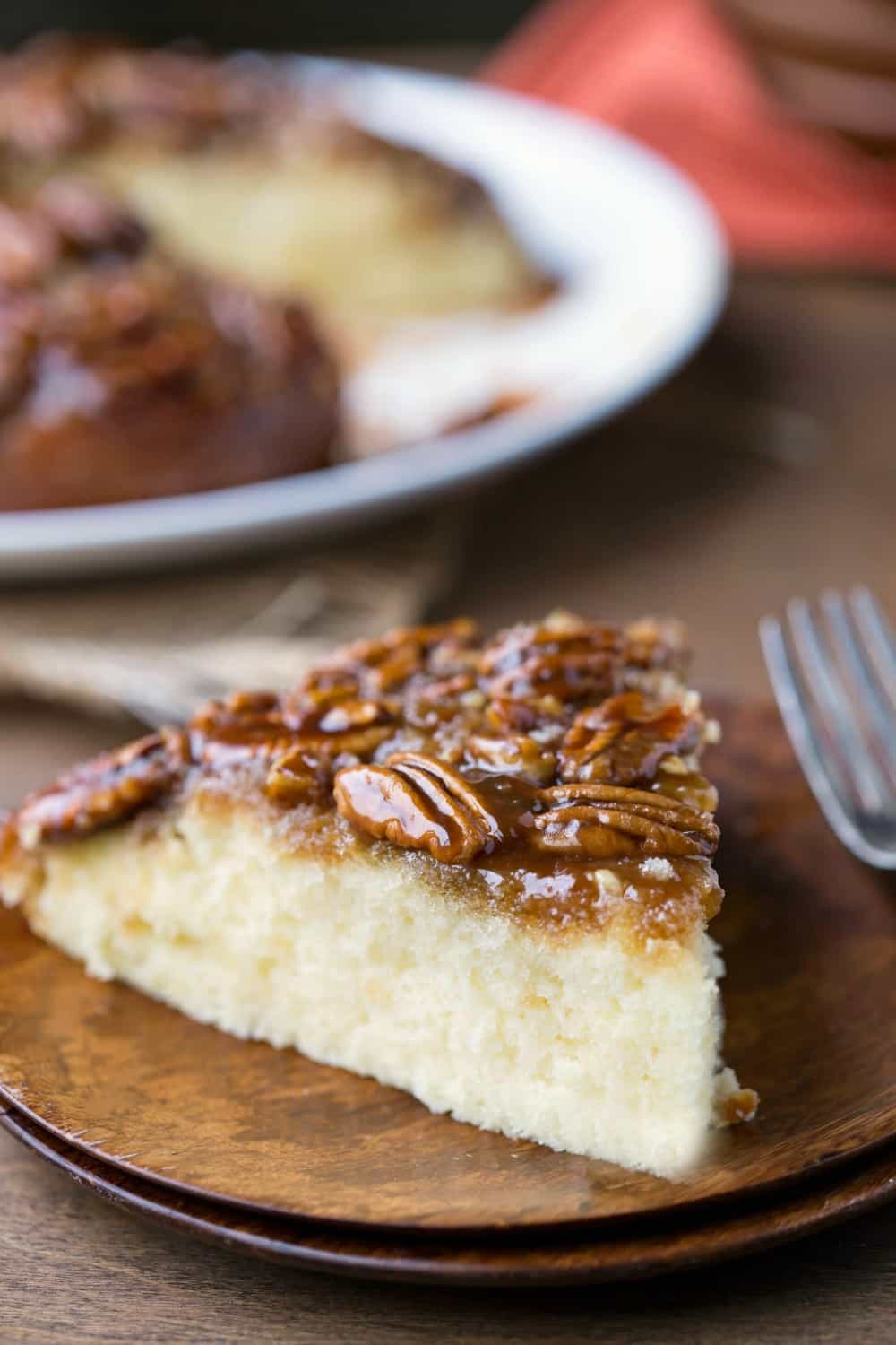 Slice of Pecan Pie Upside-Down Cake on two stacked wooden plates