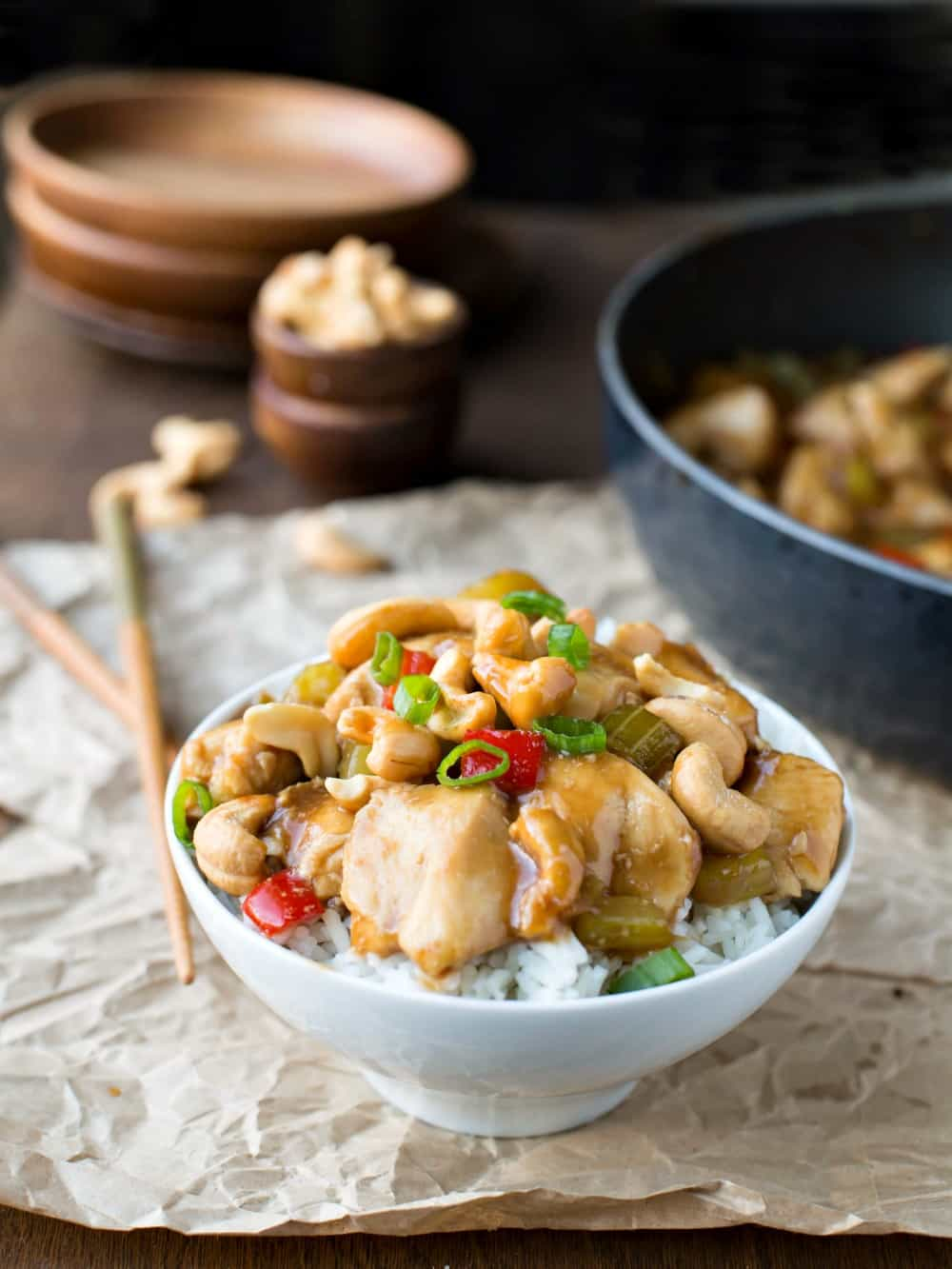 Bowl of cashew chicken topped with cashews and sliced green onions