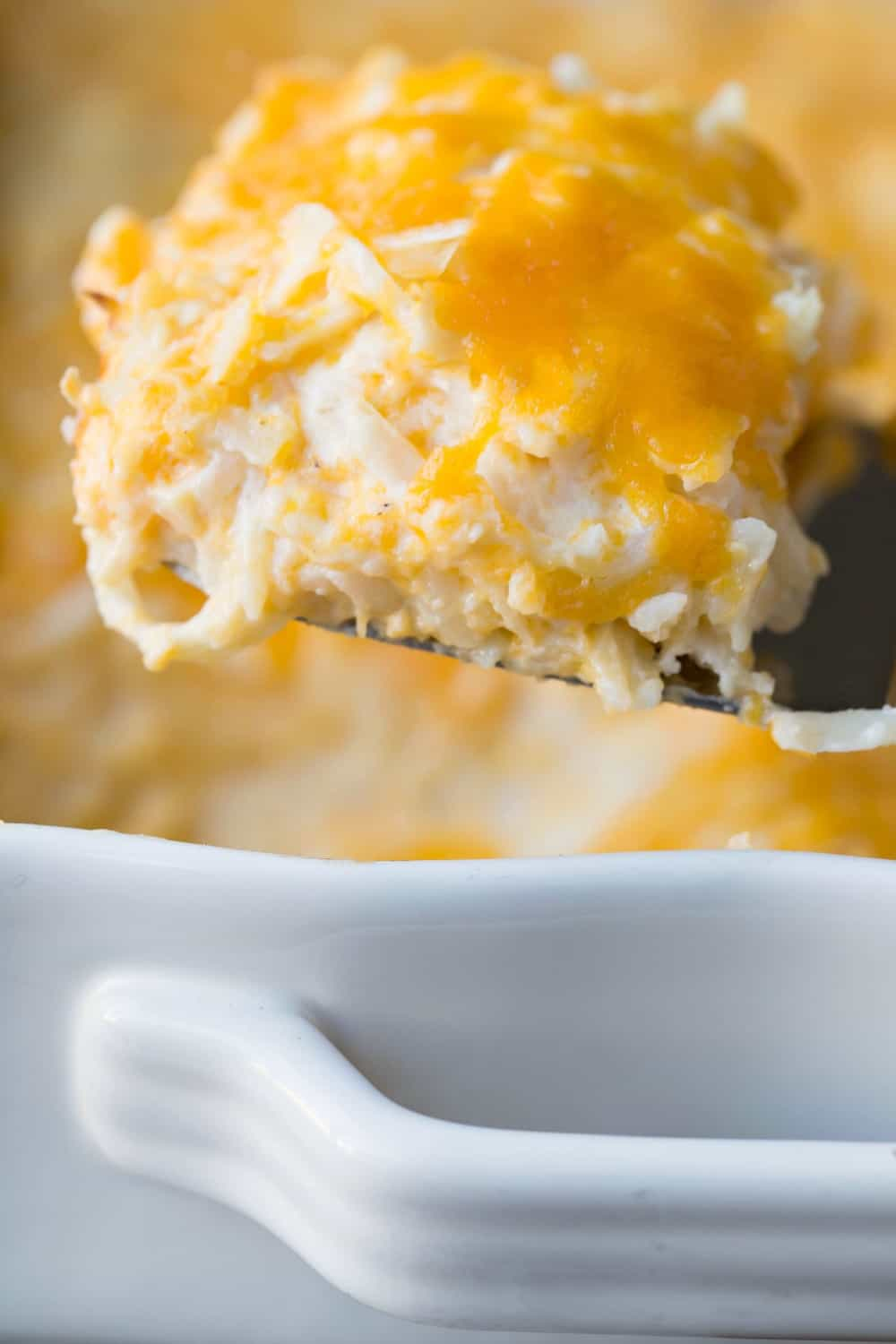Scoop of funeral potatoes on a metal spatula