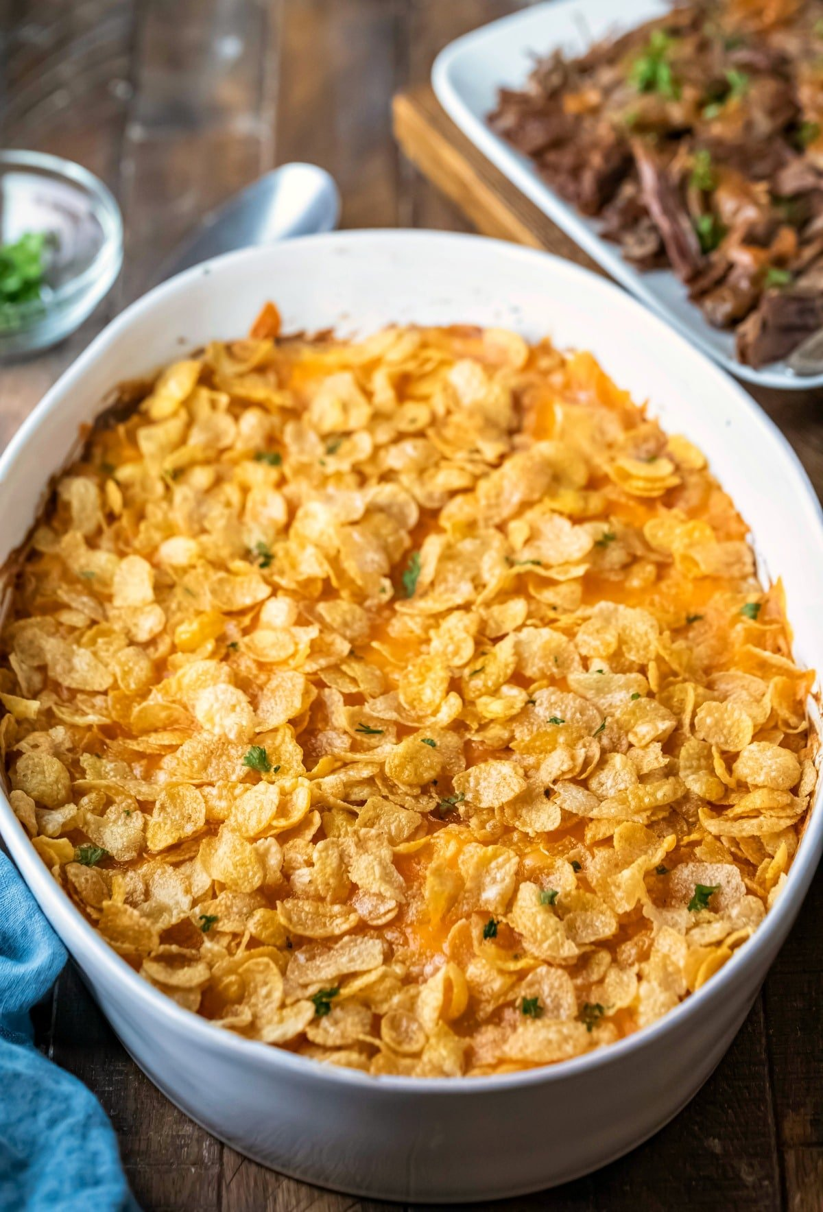 Funeral potatoes topped with cornflakes and parsley