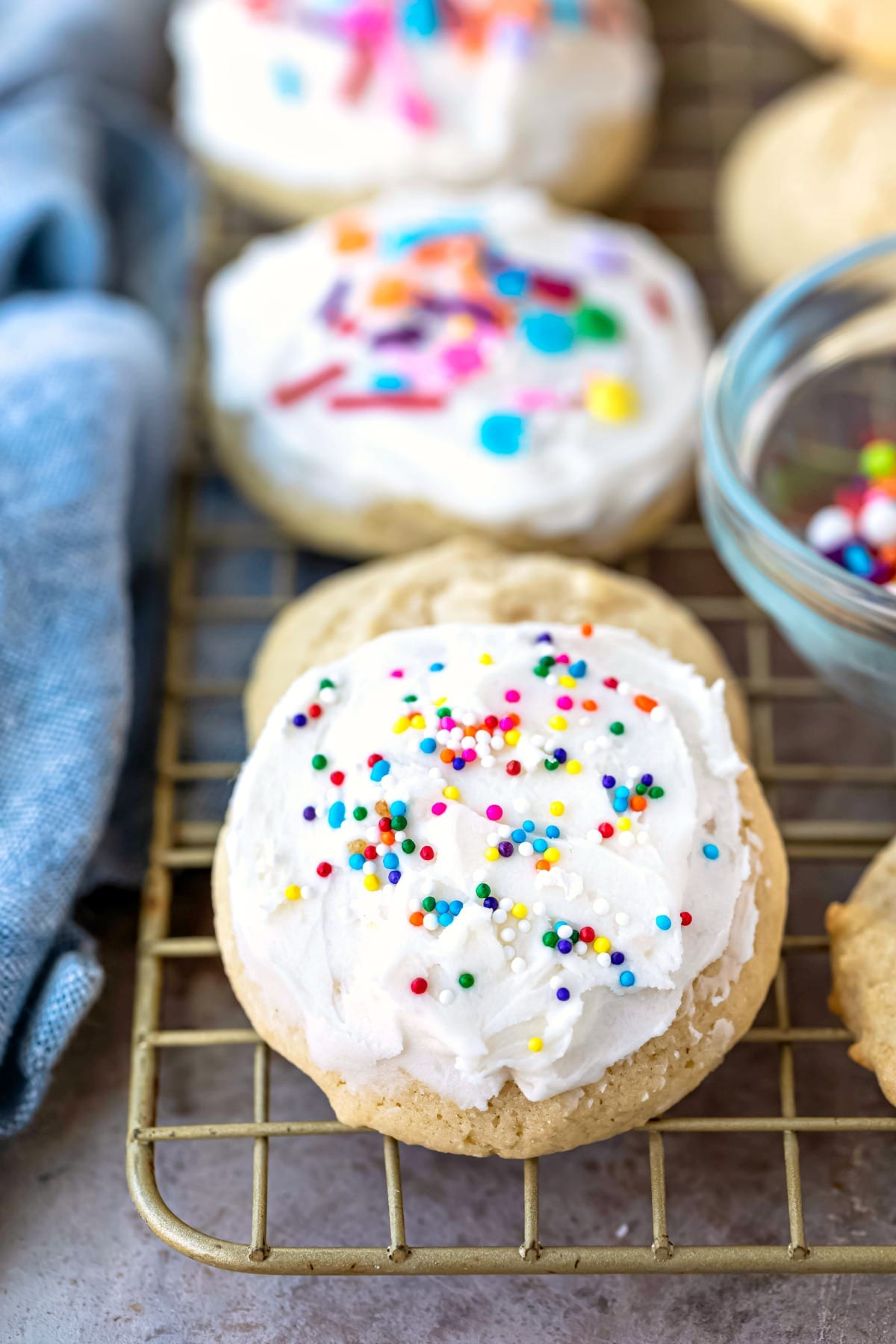 Frosted sour cream sugar cookies on a gold cooling rack