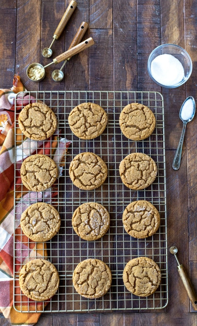 Molasses cookies on a gold cooling rack next to a dish of sugar