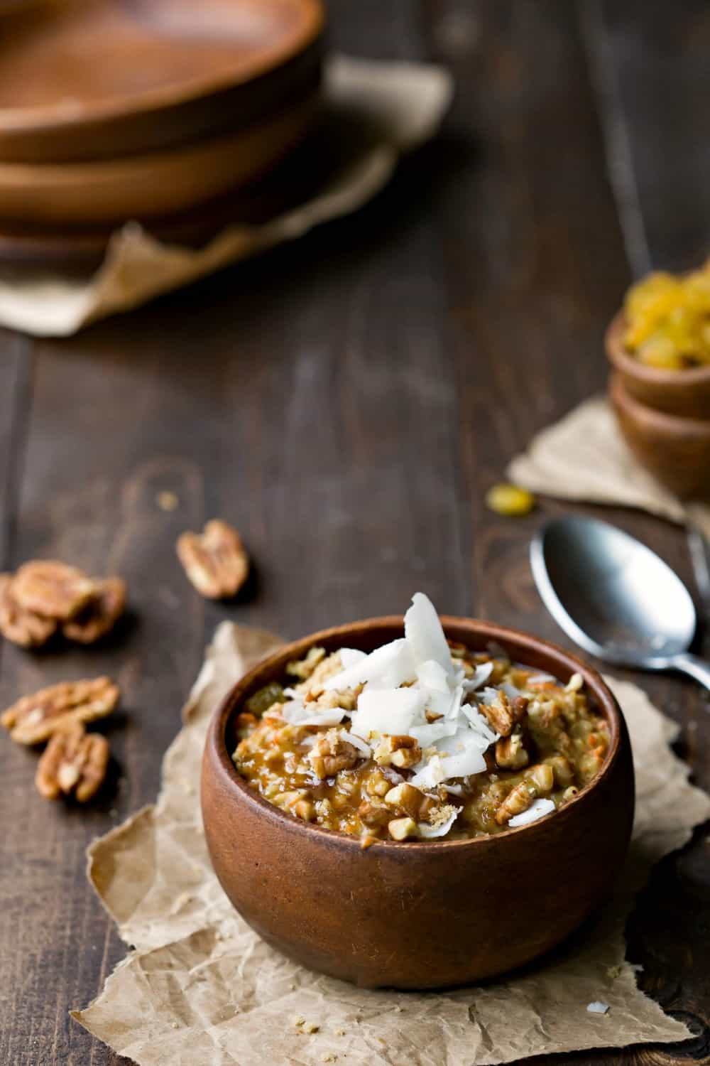 Crock Pot Carrot Cake Oatmeal topped with coconut and chopped pecans in a wooden bowl