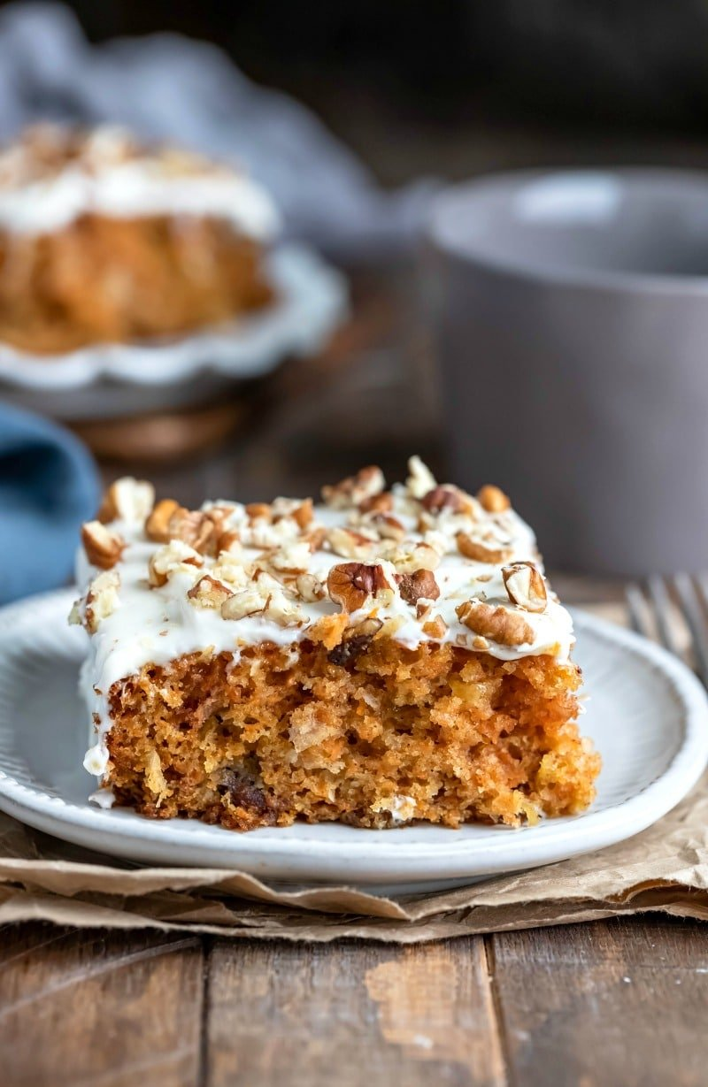 Slice of carrot cake topped with cream cheese frosting and pecans