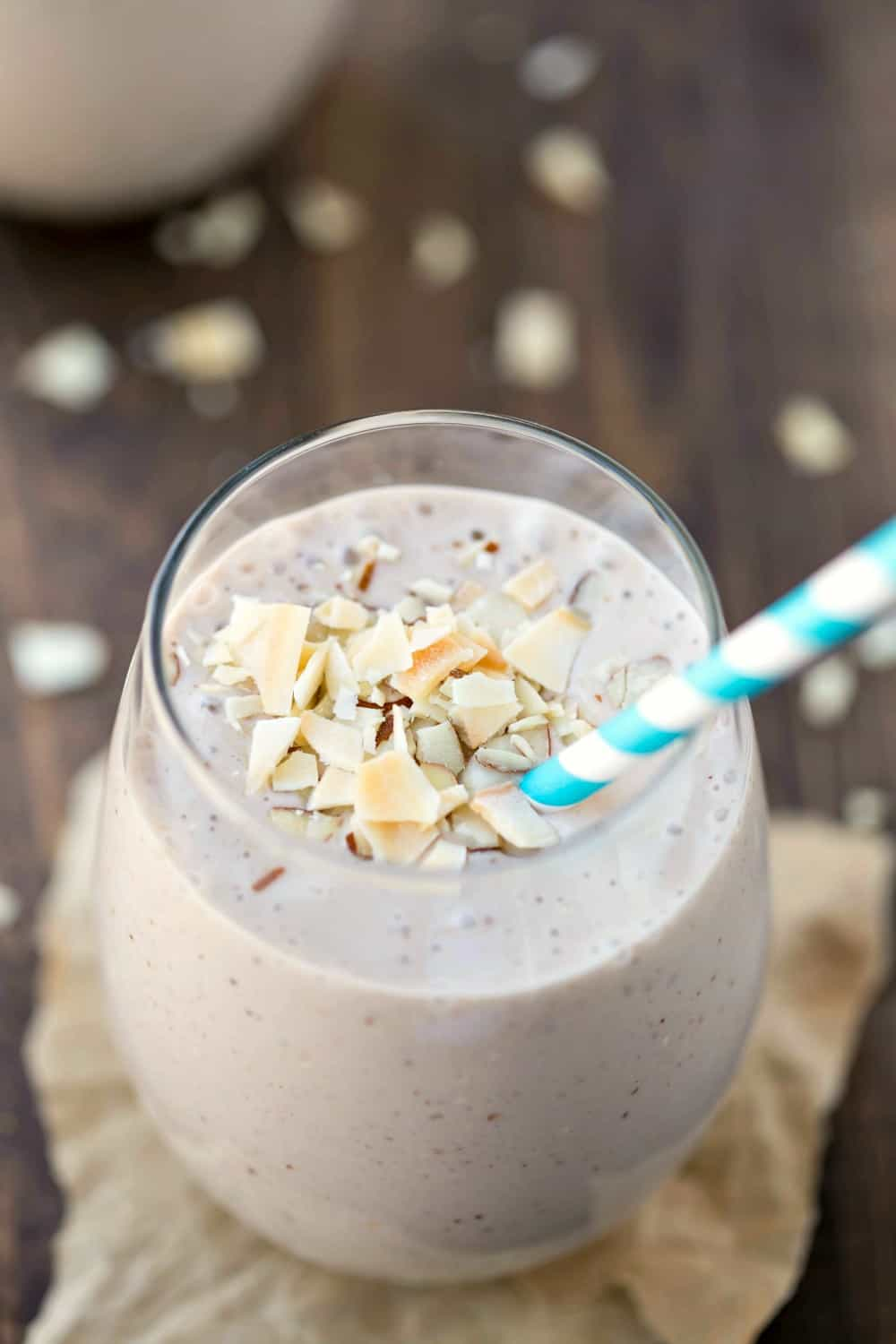 Chocolate Almond Coconut Banana Smoothie in a glass with a blue striped straw