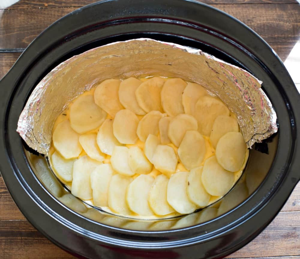 Slices of potato in a slow cooker insert