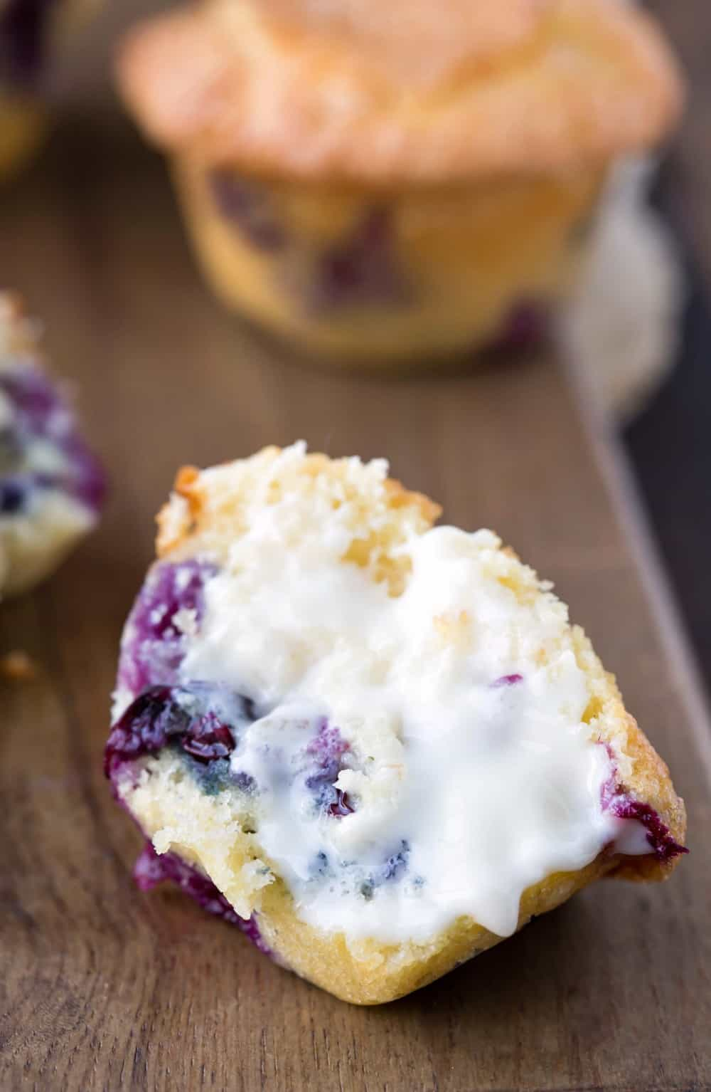 Half of a buttered Bakery Style Blueberry Muffin on a wooden cutting board