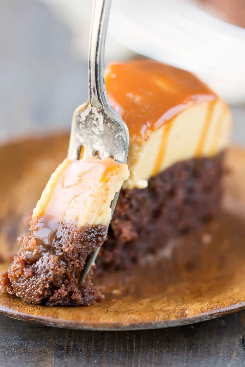 Slice of chocoflan drizzled with caramel on a wooden plate