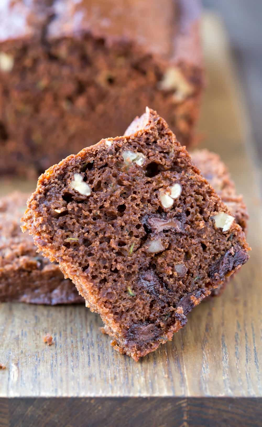 Slice of Chocolate Zucchini Bread on a wooden cutting board