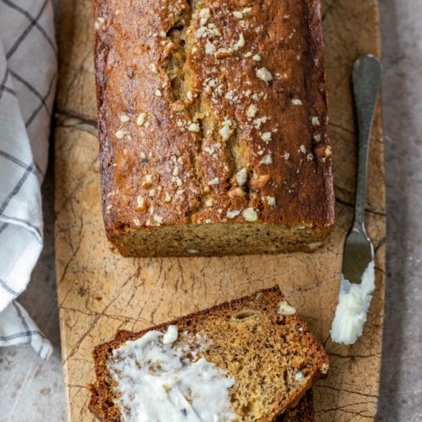 Half buttered slice of banana bread on a marble cutting board