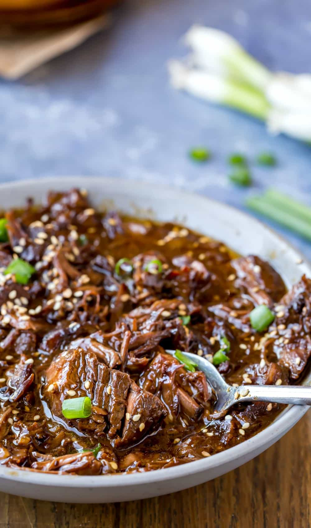 Scooping Slow Cooker Korean Beef with a silver spoon
