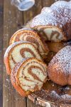 pieces of cinnamon swirl bundt cake on a wooden plate
