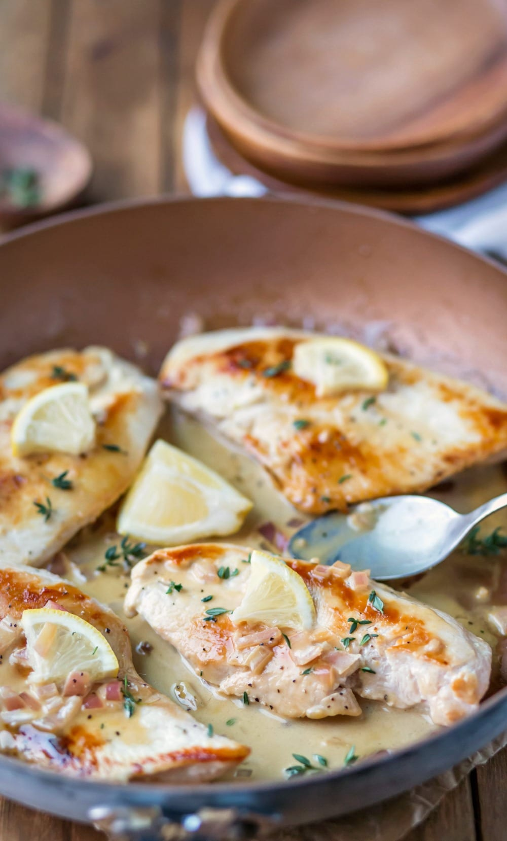 One Skillet Creamy Lemon Garlic Chicken next to a silver spoon and a lemon wedge in a skillet
