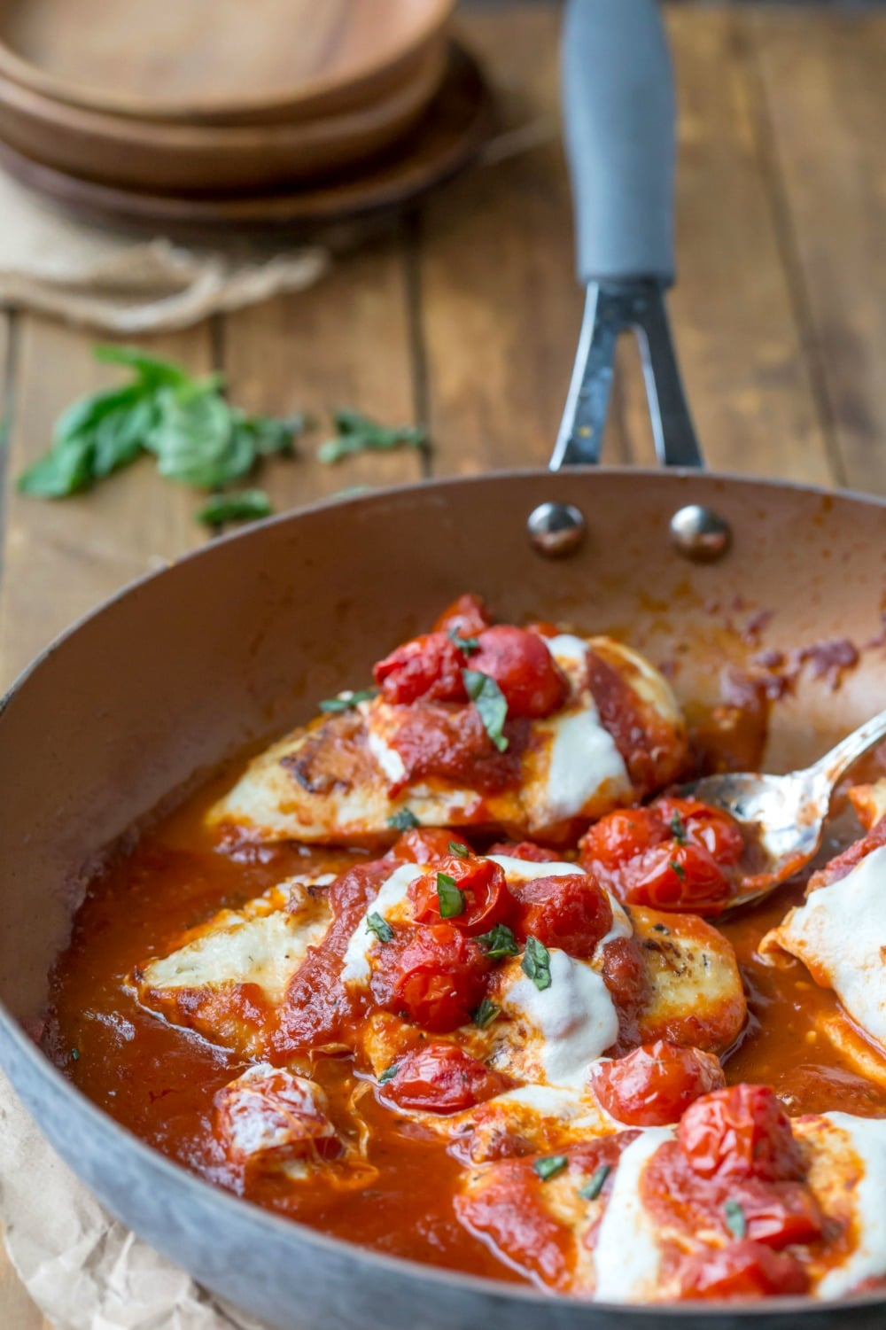 Skillet chicken parmesan in the pan with basil and plates behind it