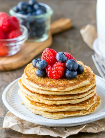 Cottage cheese pancakes next to berries and pitcher