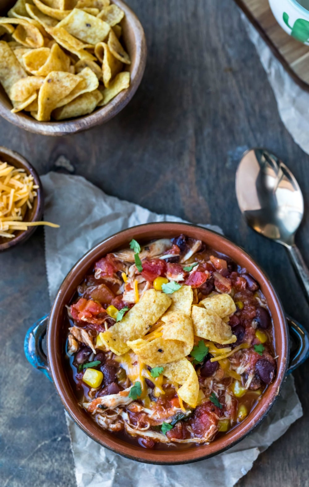 Slow Cooker Chicken Frito Chili in a blue bowl next to a bowl of fritos