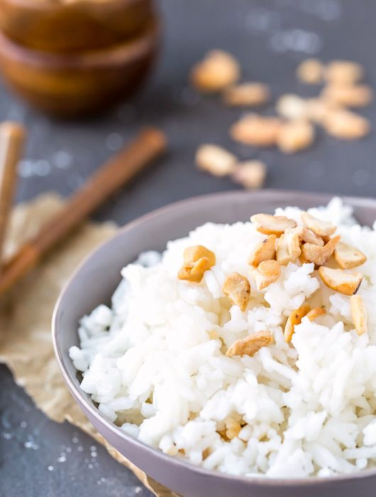 Coconut rice in a blue bowl topped with cashew pieces