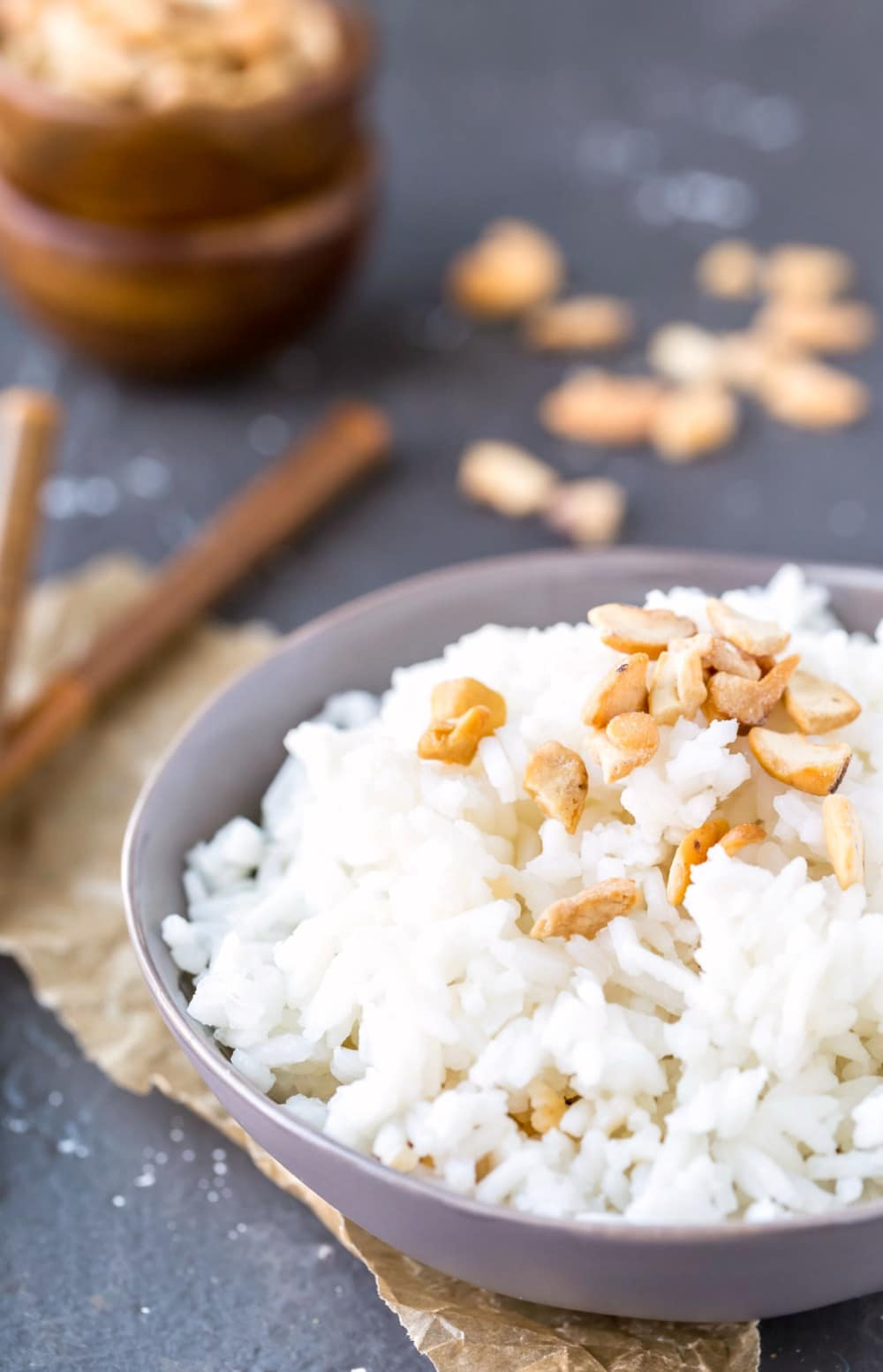 Coconut rice in a blue bowl topped with pieces of cashew