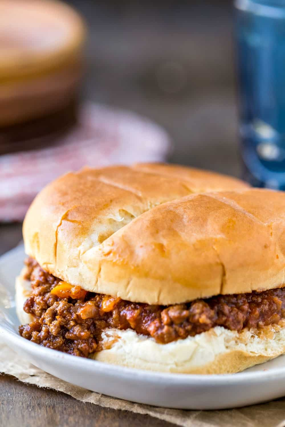 Crock pot sloppy joes on a white plate next to a blue glass