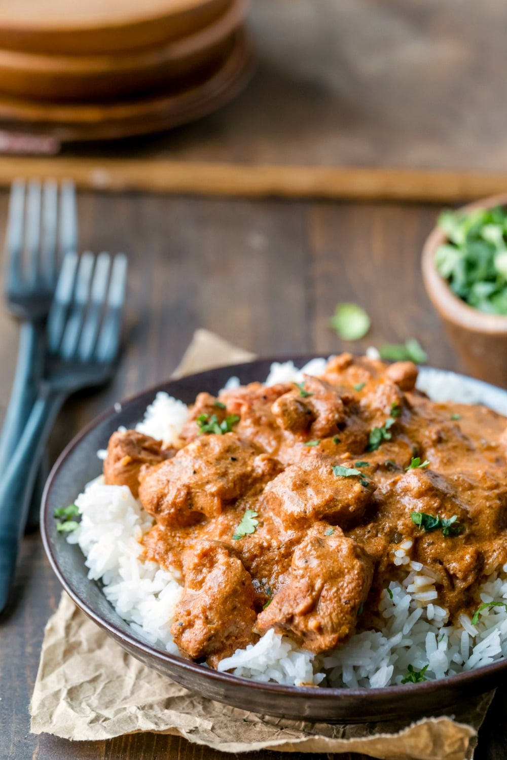 Indian Butter Chicken over rice in a dark brown dish
