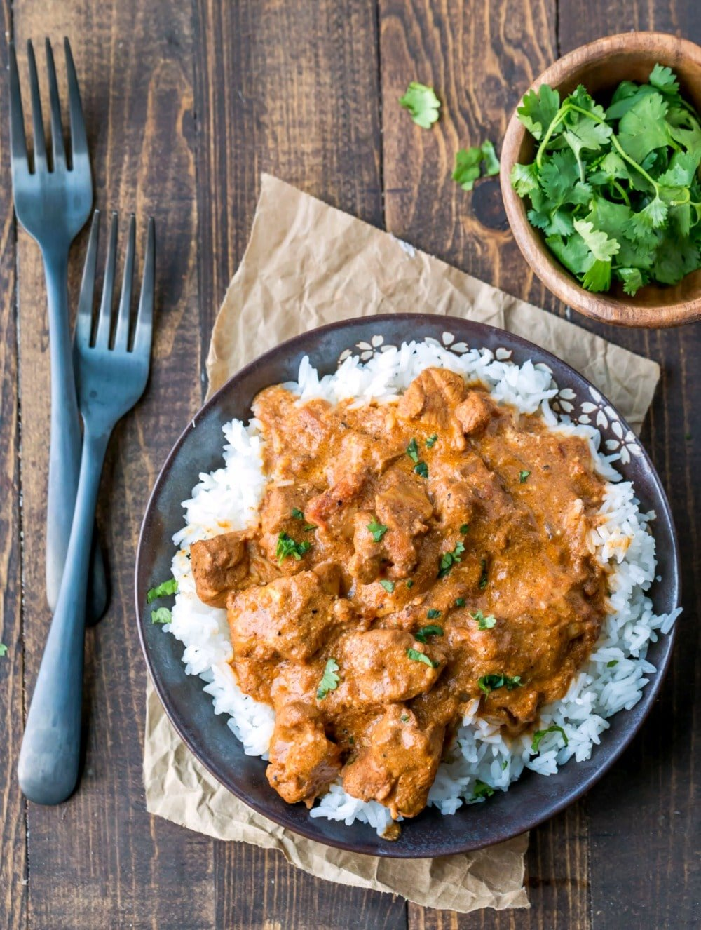 Dish of Indian Butter Chicken next to two dark metal forks