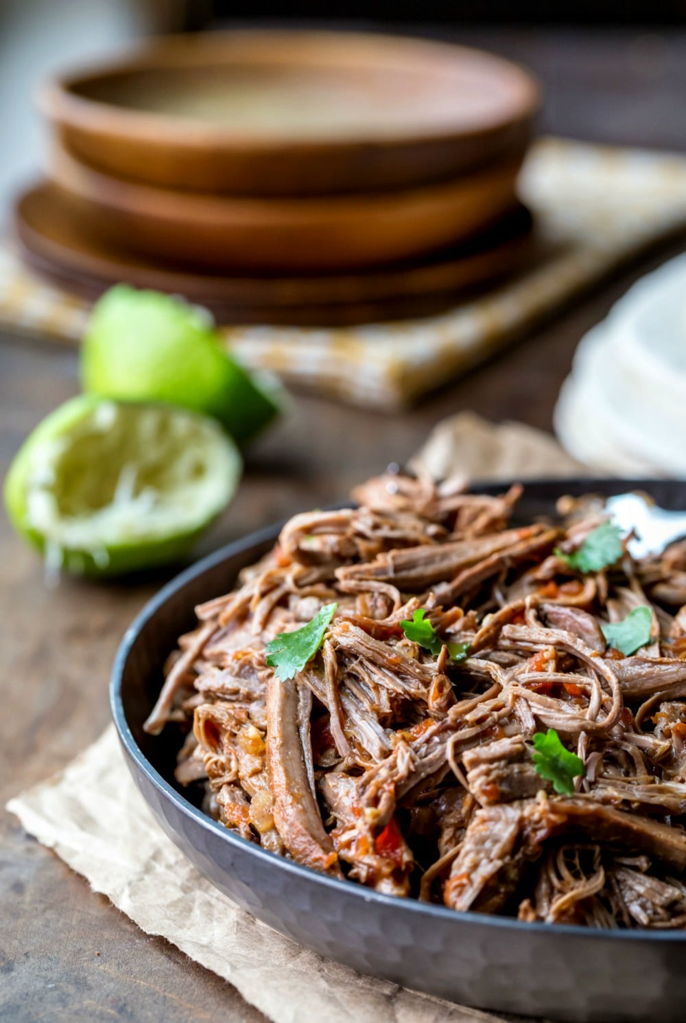 Mexican shredded beef in a metal dish next to two squeezed limes and a stack of wooden dishes