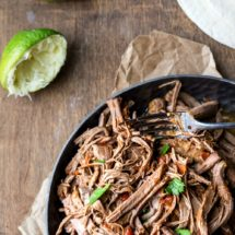 Mexican shredded beef in a metal dish next to sliced limes