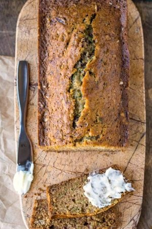 Zucchini bread on a marble cutting board next to a butter knife