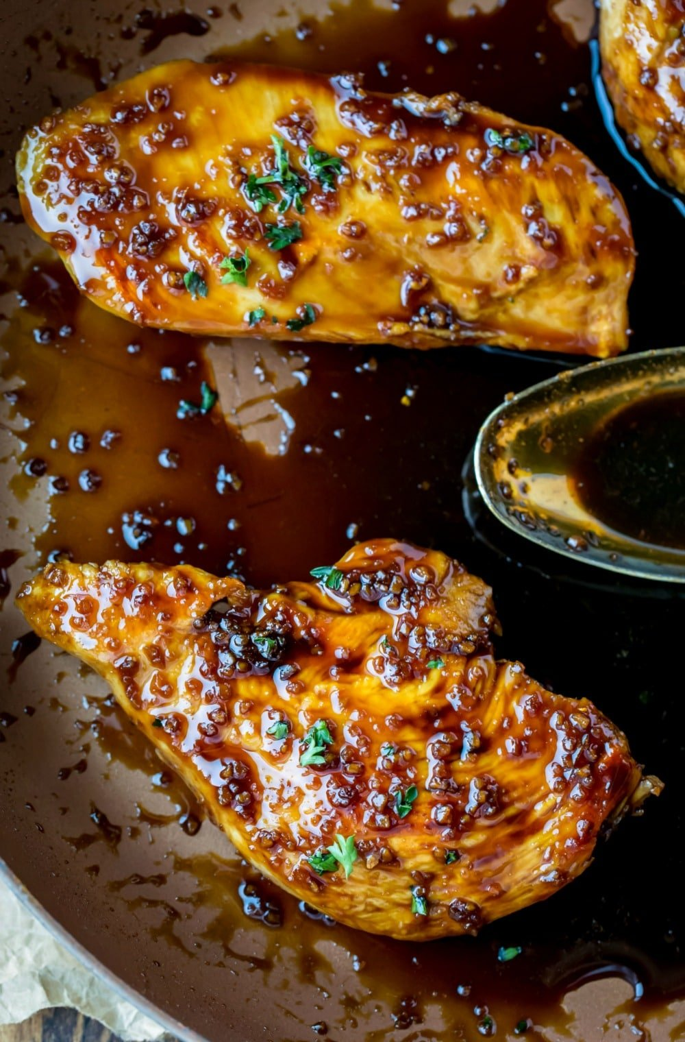 Two pieces of Honey Garlic Chicken in a skillet with sauce