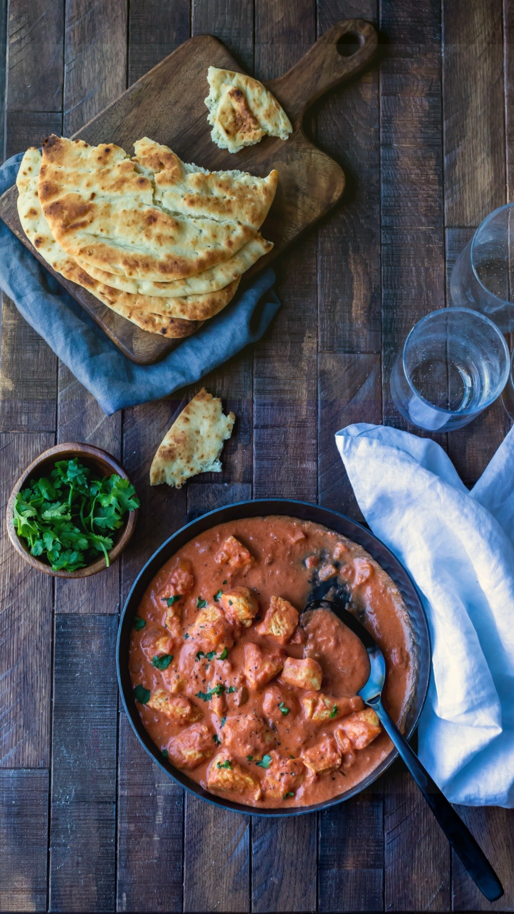 Dish of easy chicken tikka masala next to a bowl of cilantro and pieces of naan