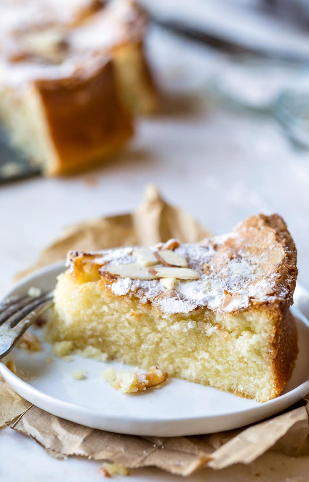Slice of olive oil cake on a white next next to a fork