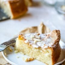 Slice of olive oil cake topped with powdered sugar and sliced almonds
