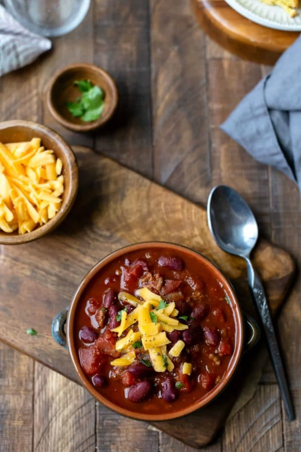 Crock of chili on a wooden cutting board