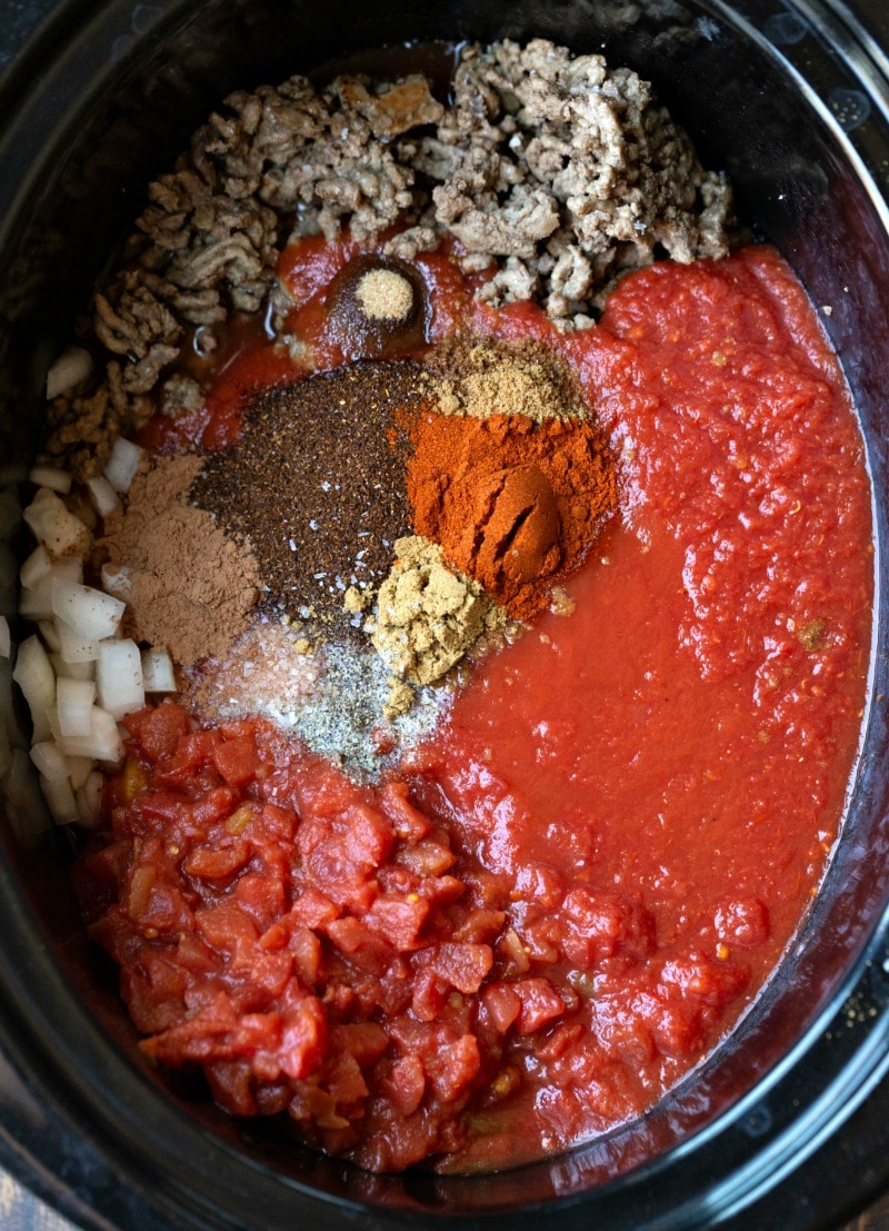 Crockpot chili ingredients in a slow cooker insert