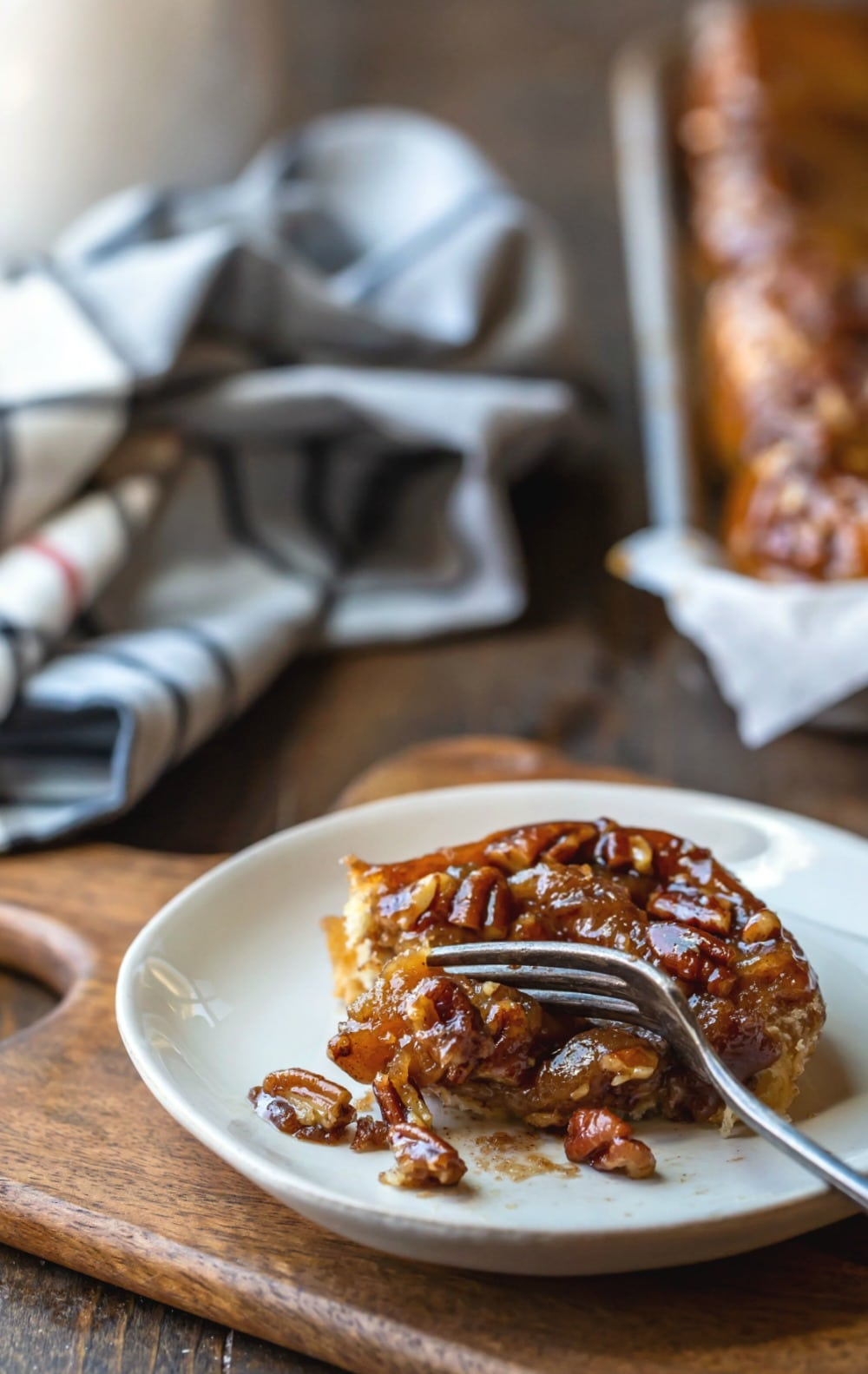 Easy sticky Bun on an off-white plate with a fork taking a bite
