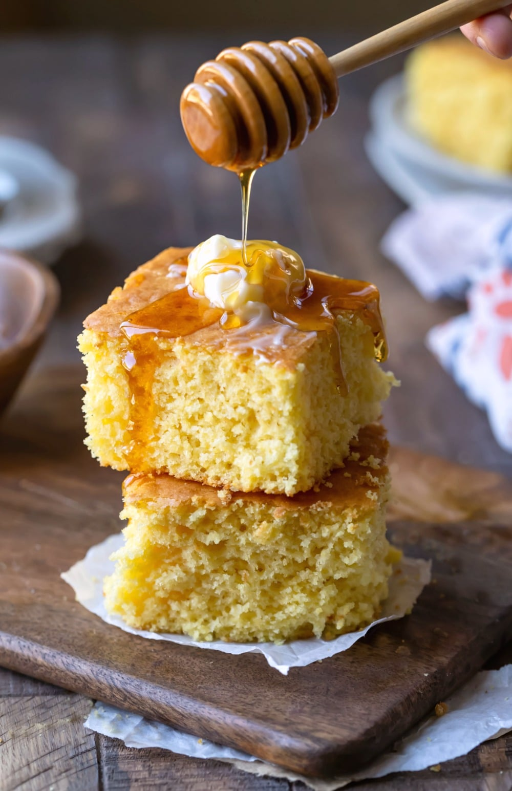 Stacked pieces of sweet cornbread with honey drizzled on top