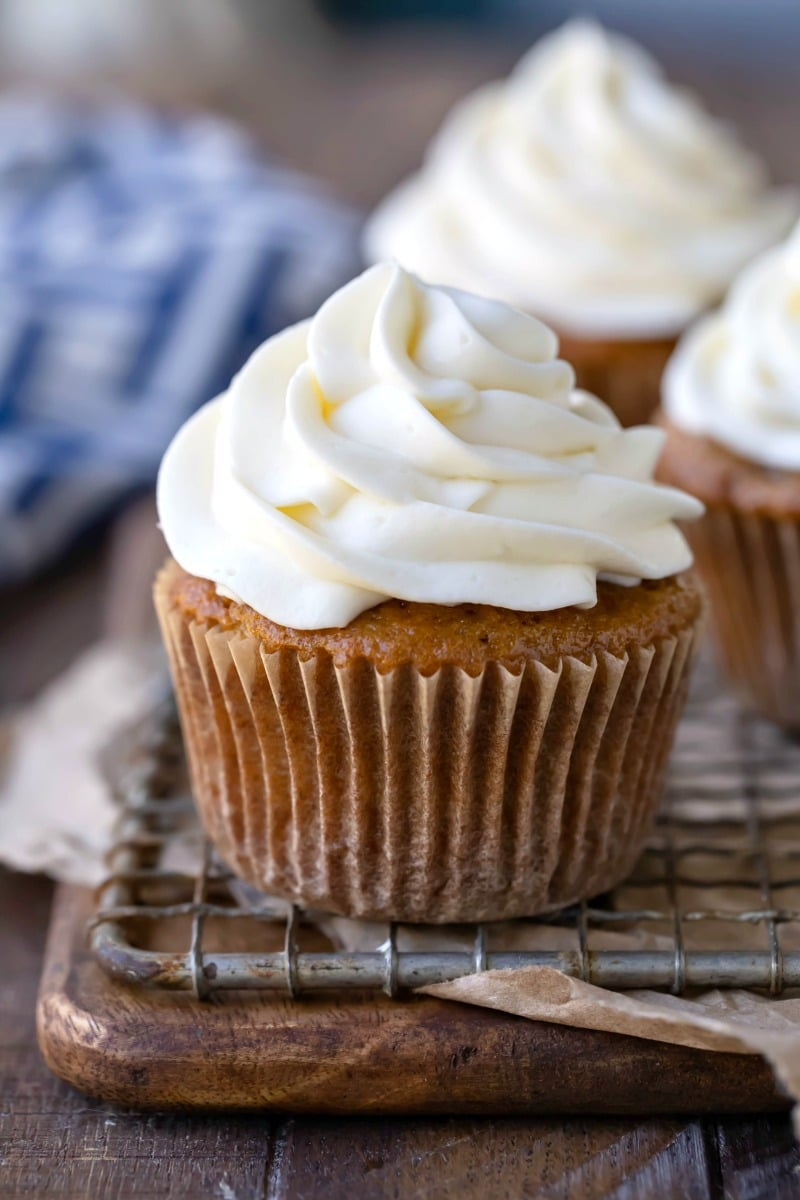 Cream cheese frosting on a cupcake sitting on a wire cooling rack